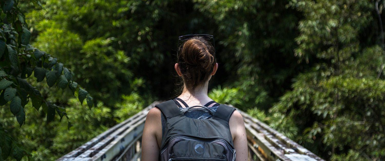 Woman with backpack walking on bridge