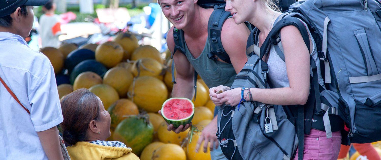 Backpackers buying fruit in Vietnam
