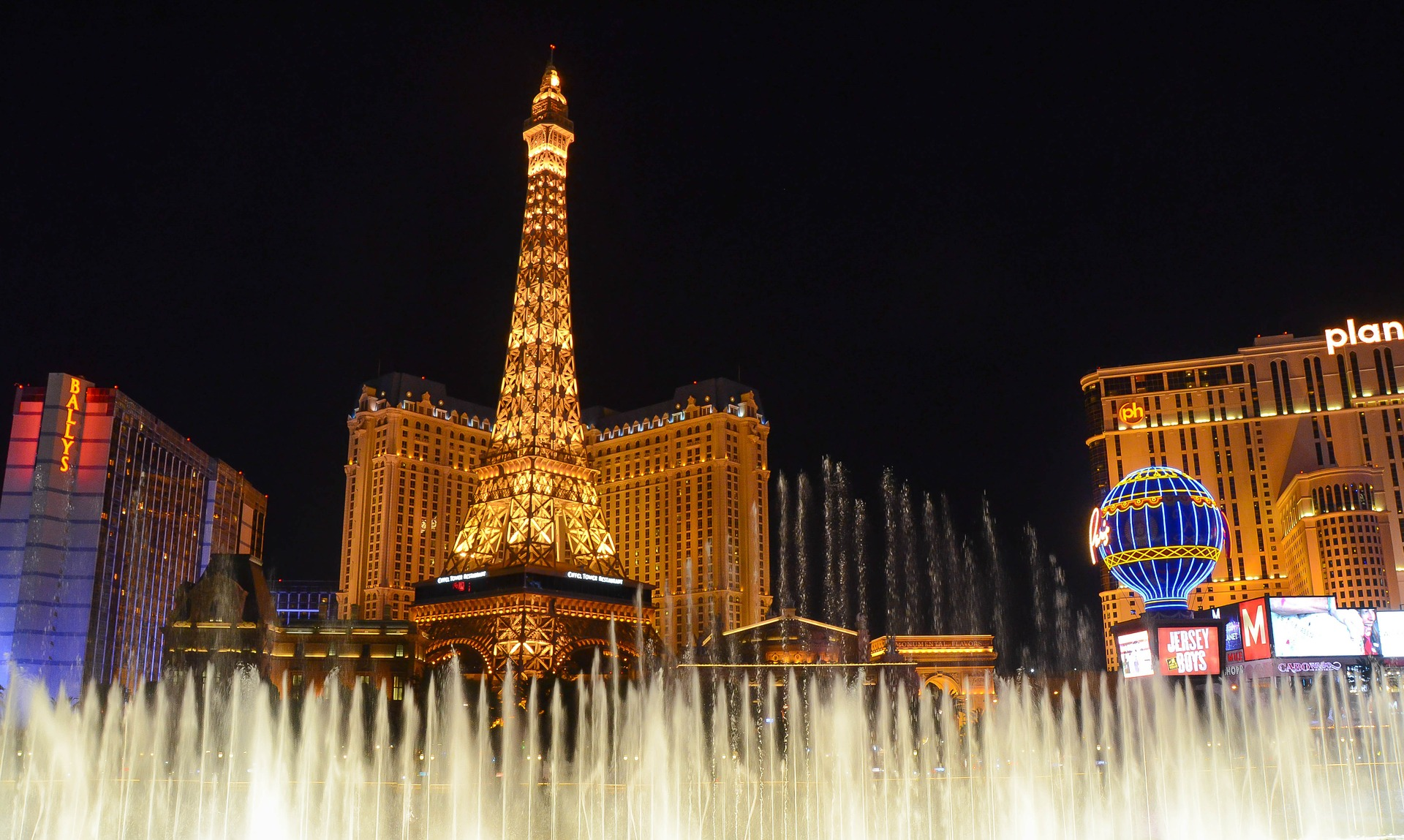 Bellagio's lakefront dancing fountains in Las Vegas, with the Eiffel Tower Experience in background