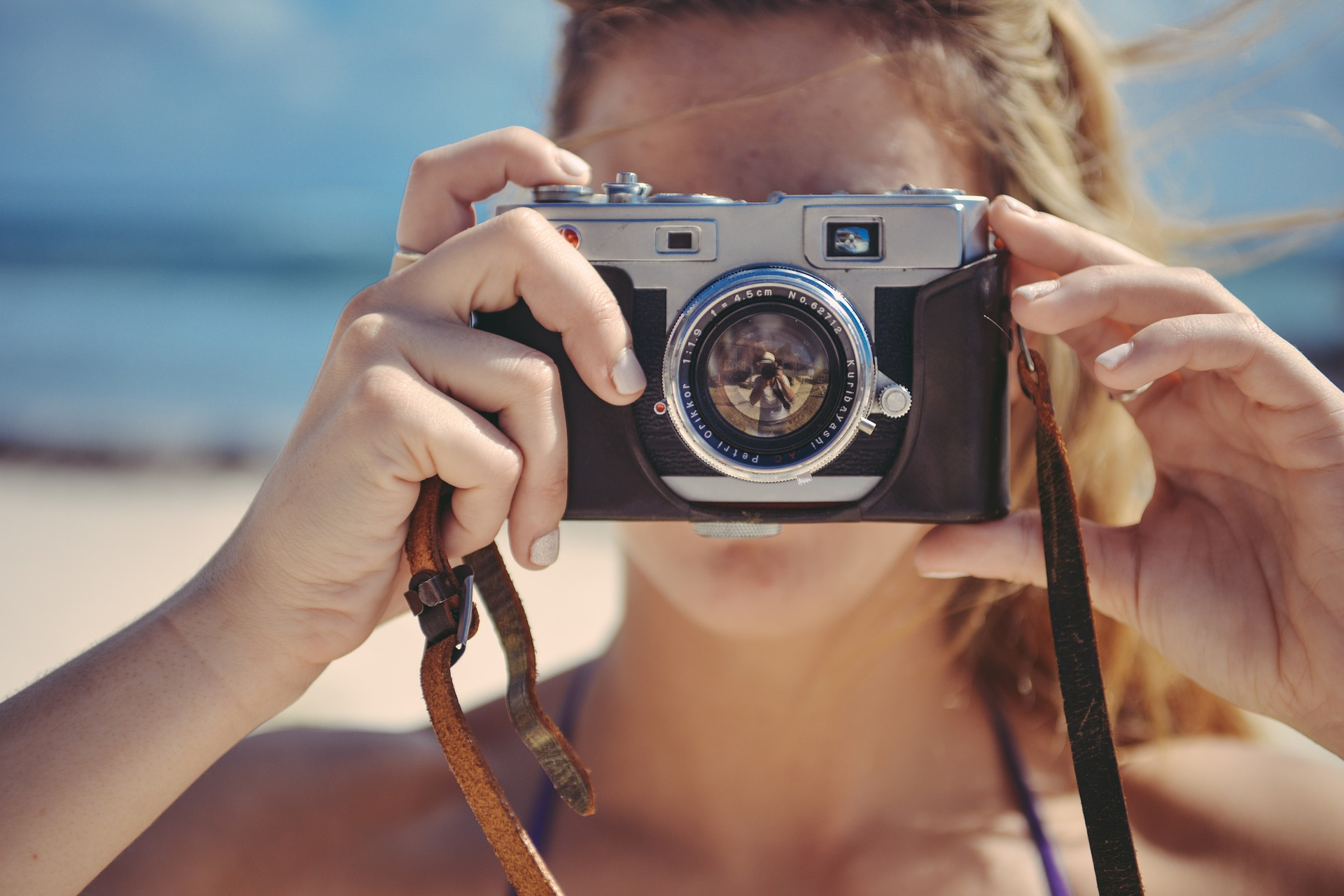 Blonde girl with camera taking picture