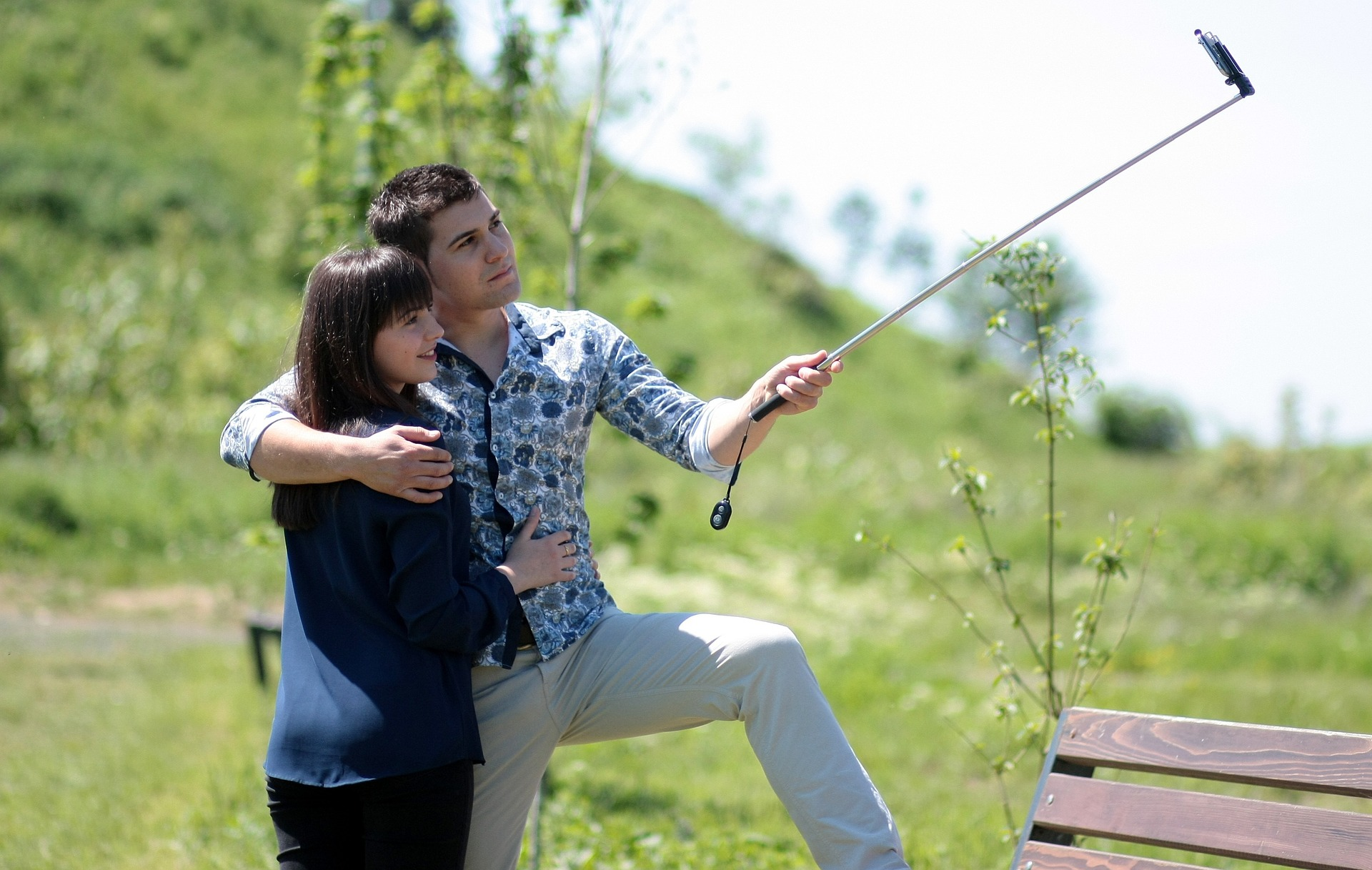 Couple outdoors taking photo with selfie stick