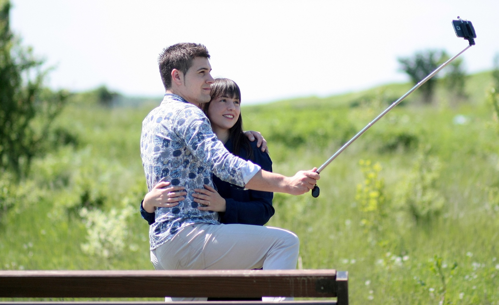 Couple taking photo with long selfie stick