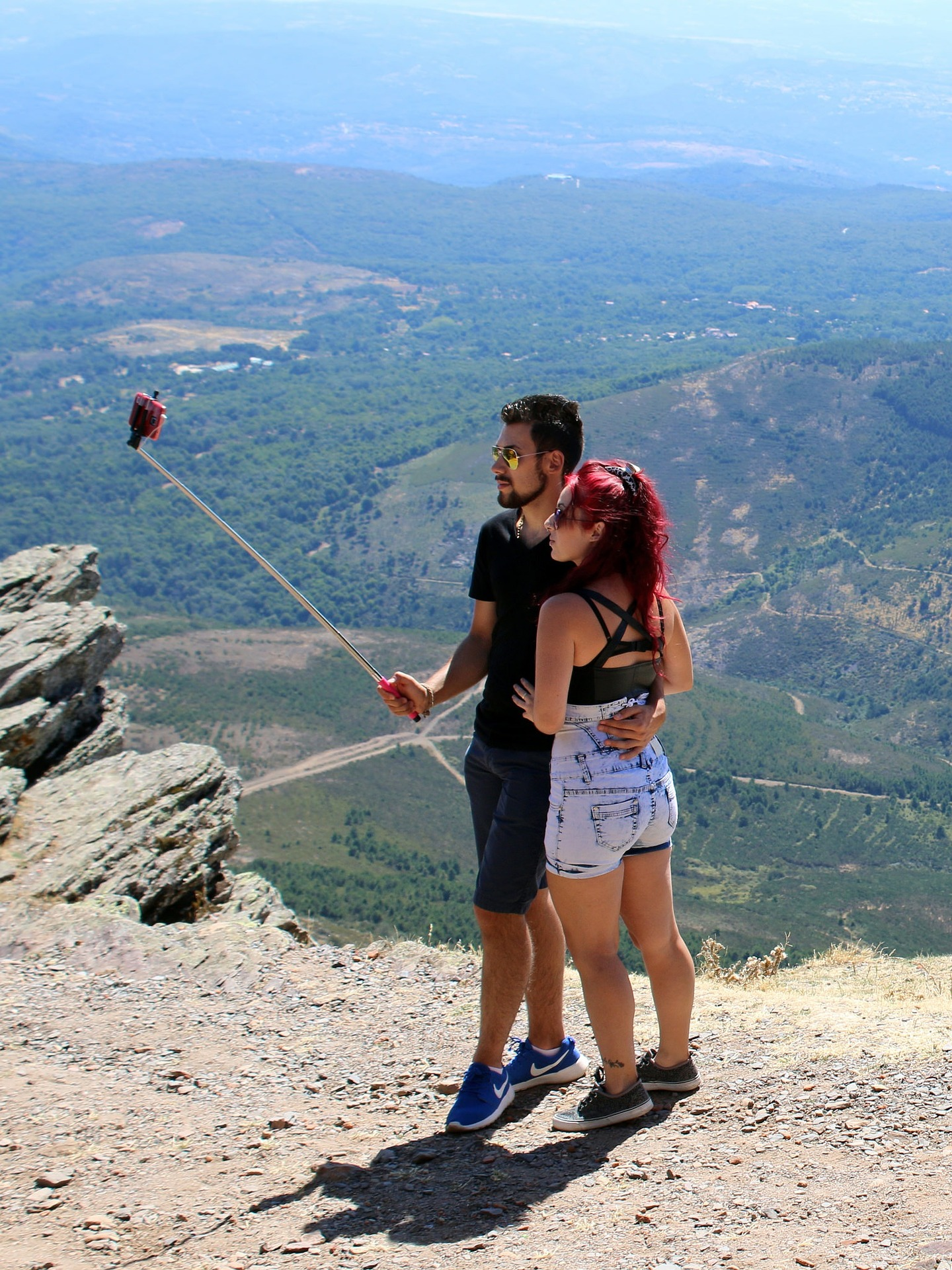 Couple taking photo with selfie stick on a hill