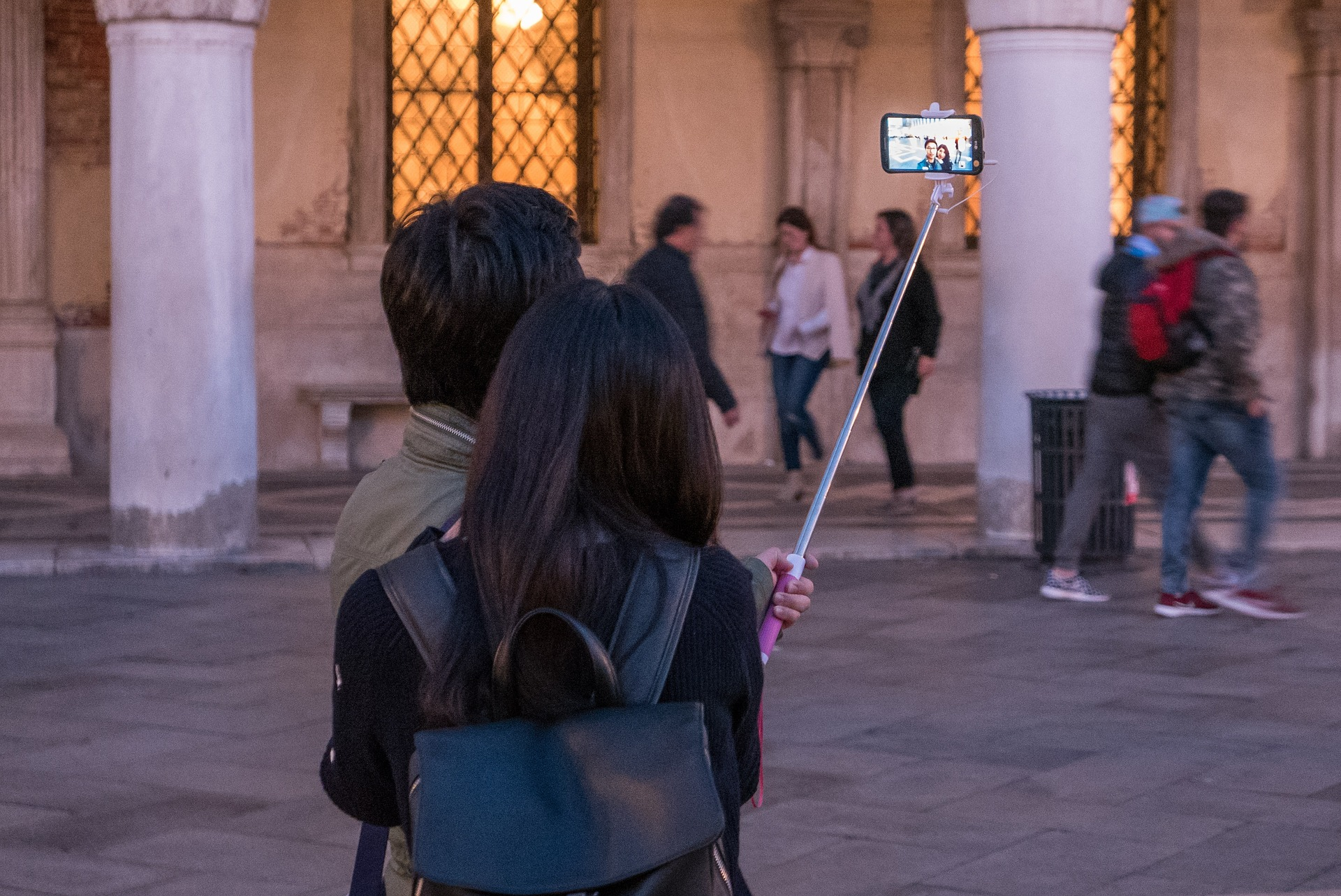Couple taking pictures infront of building with selfie stick