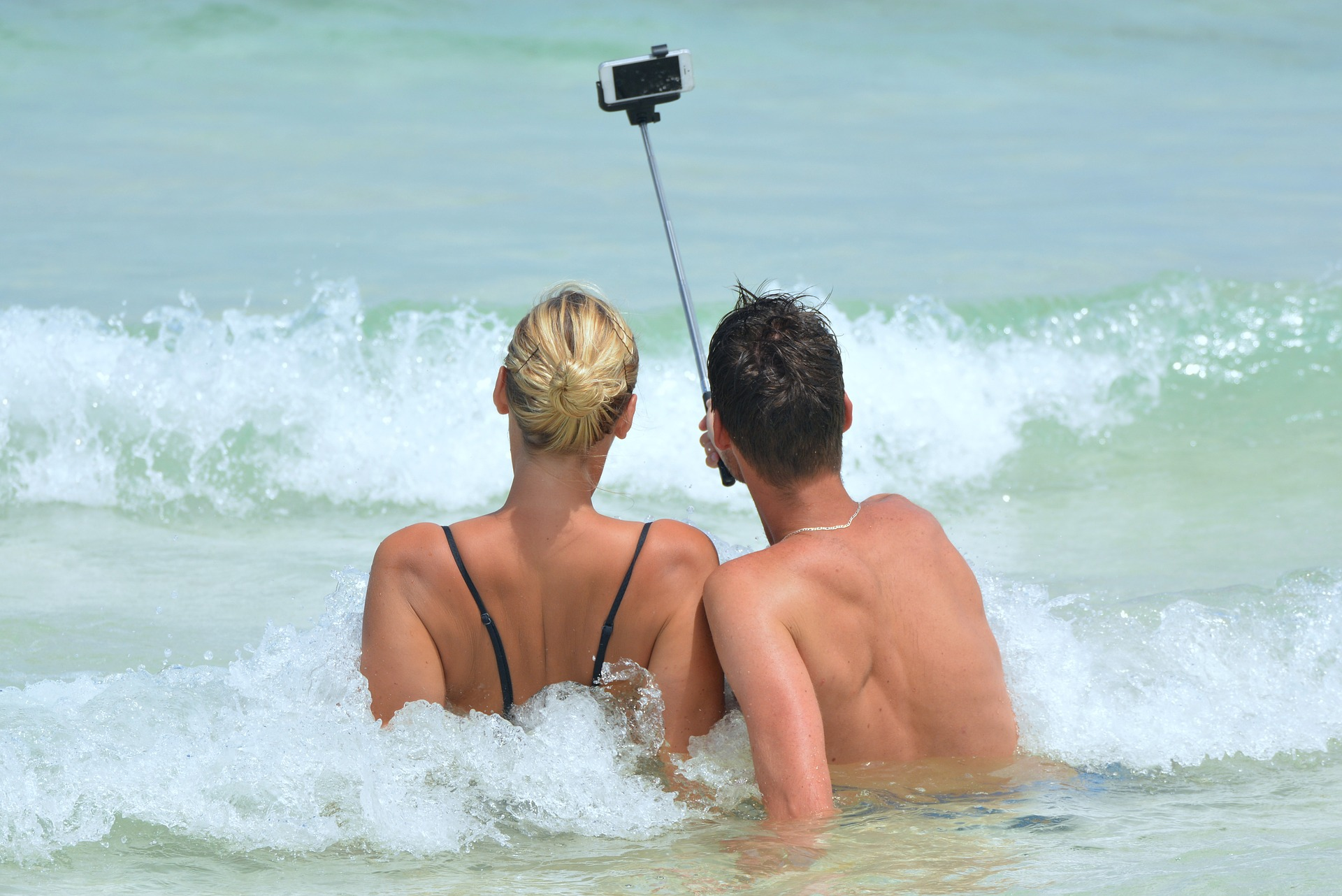 Couple with selfie stick taking photo in the sea