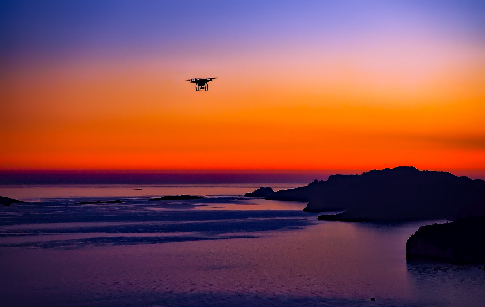 Drone flying above sea in sunset