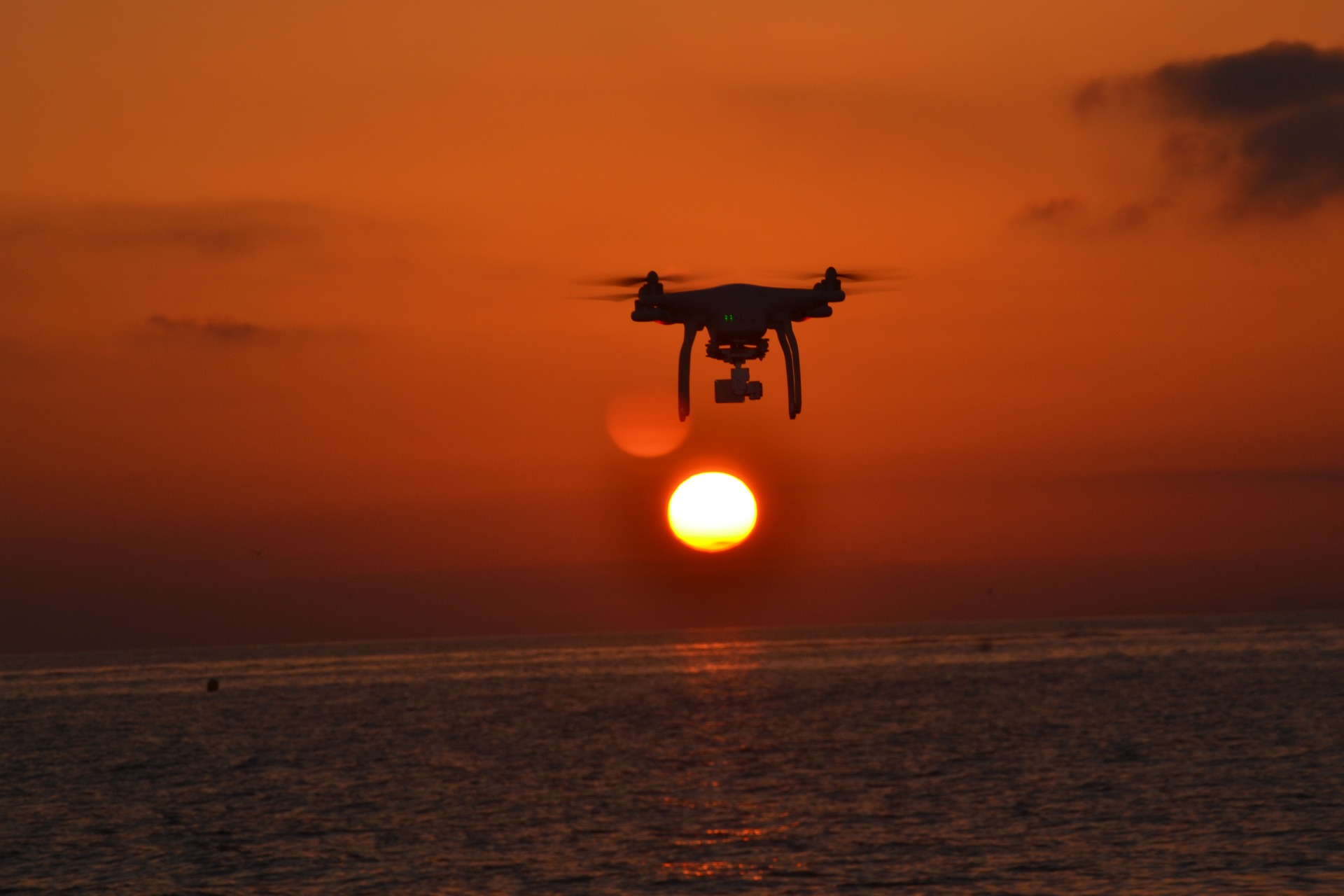 Drone flying over sea at sunset
