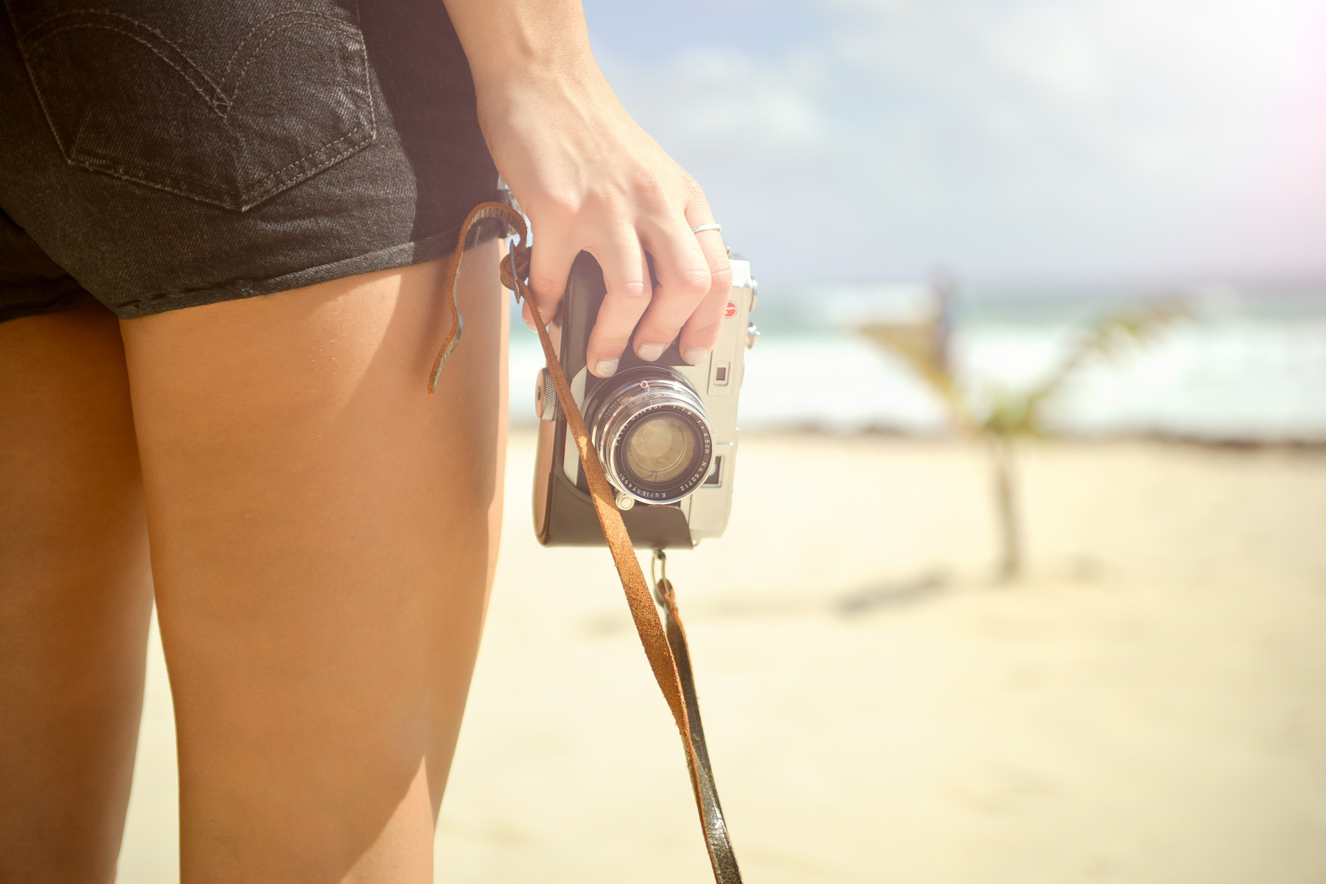 Girl with camera on the beach