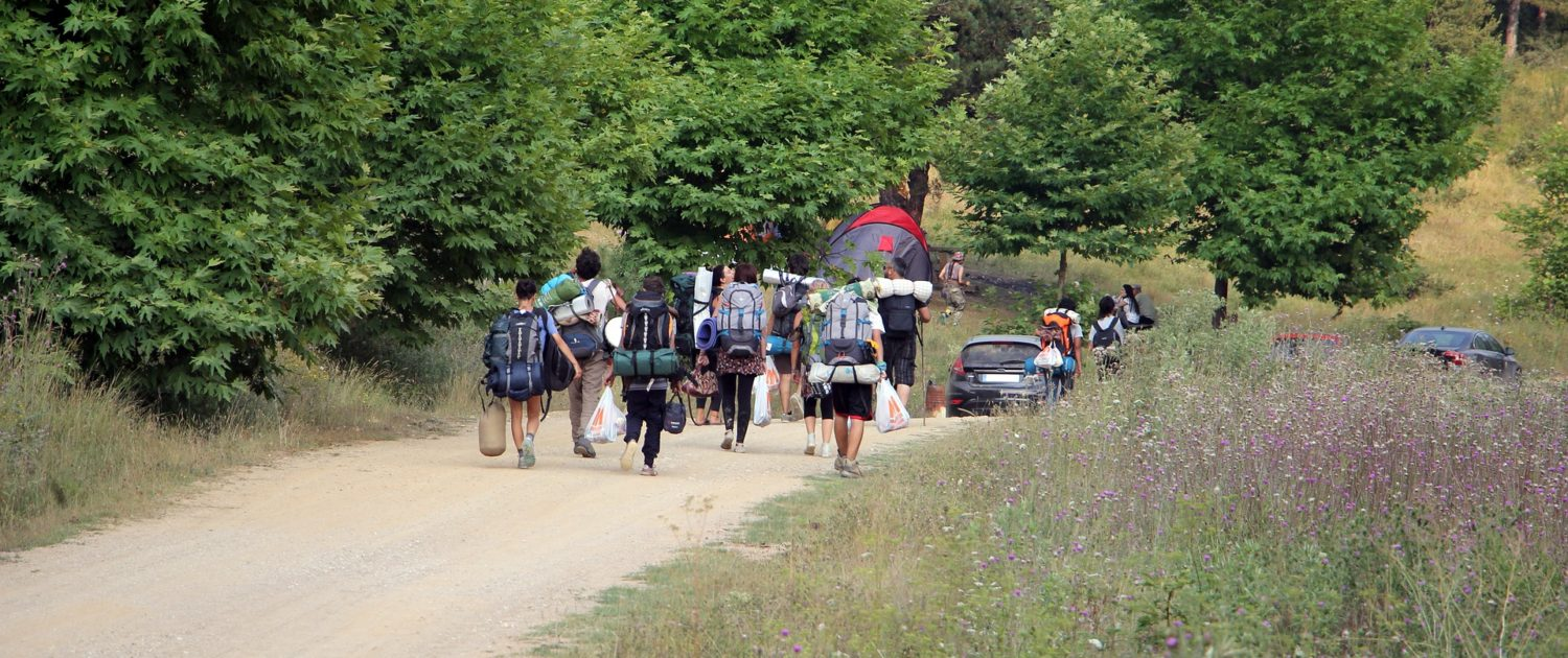 Group of backpackers walking down remote road