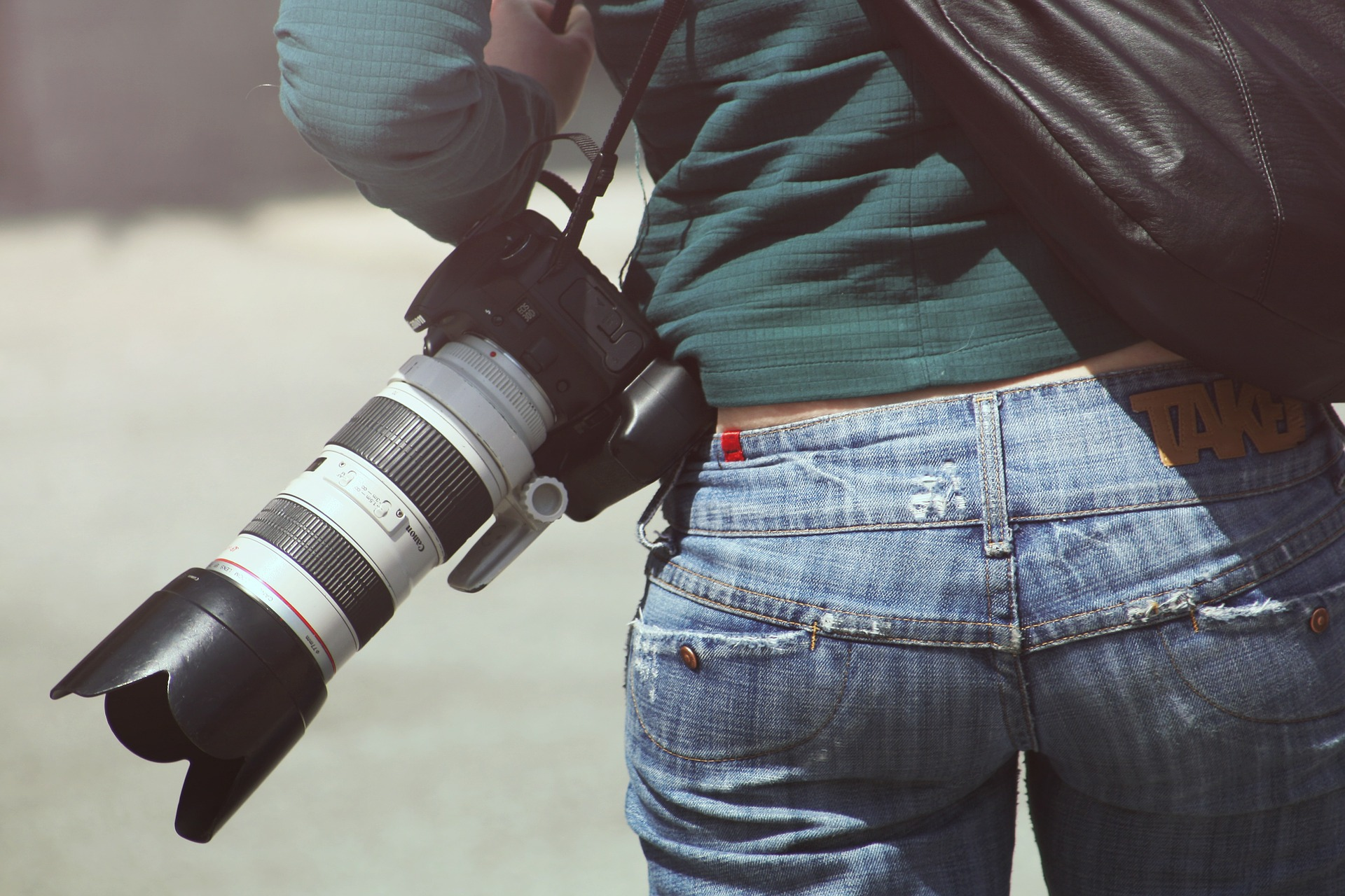 Photographer holding camera with long lens