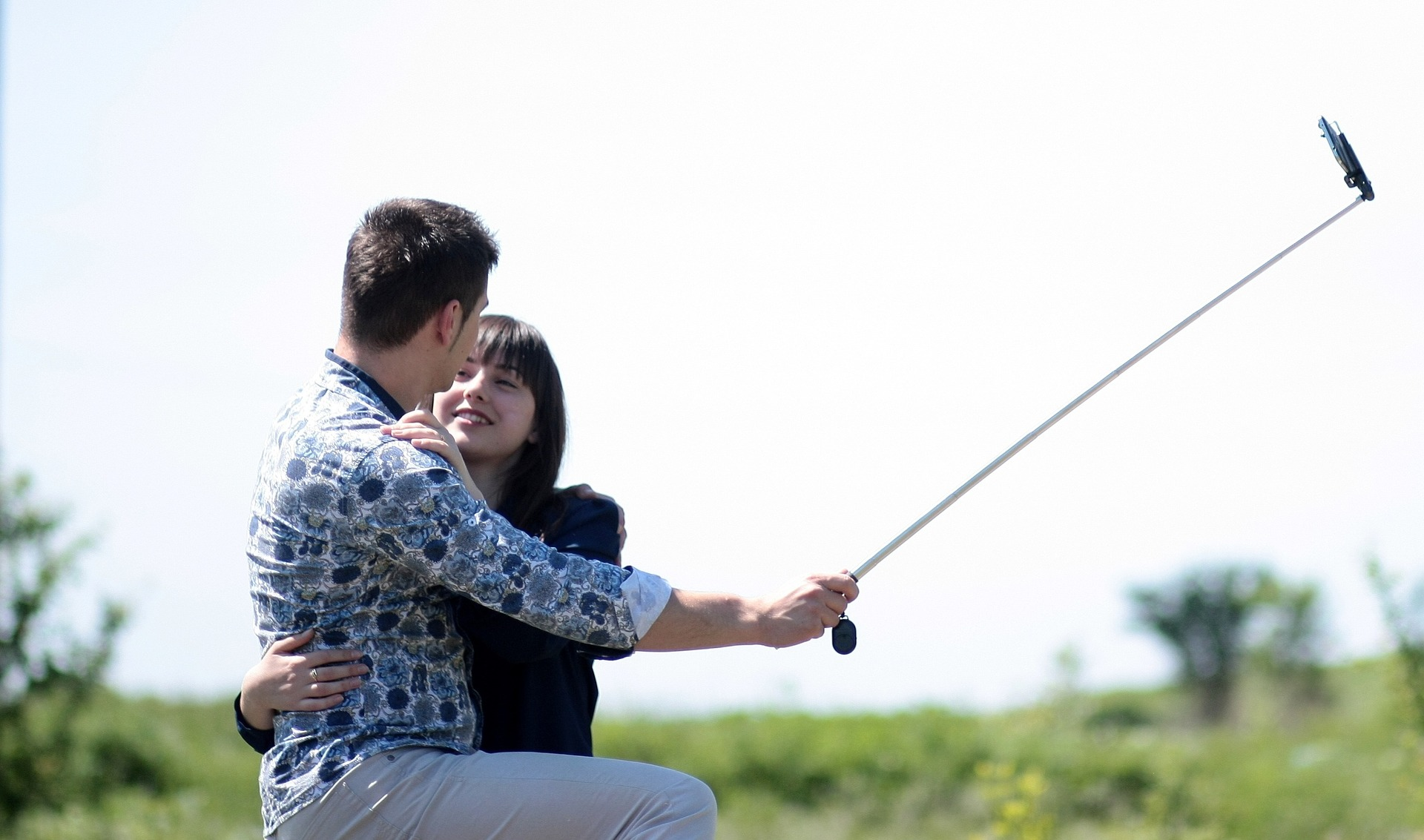 Romantic couple taking photo with selfie stick