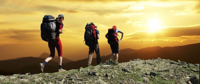 Three hikers wearing backpacks