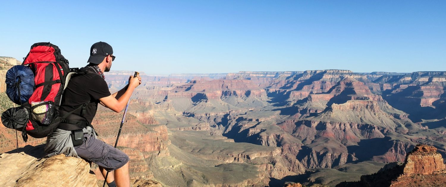 Traveller wearing backpack sitting on top of a canyon