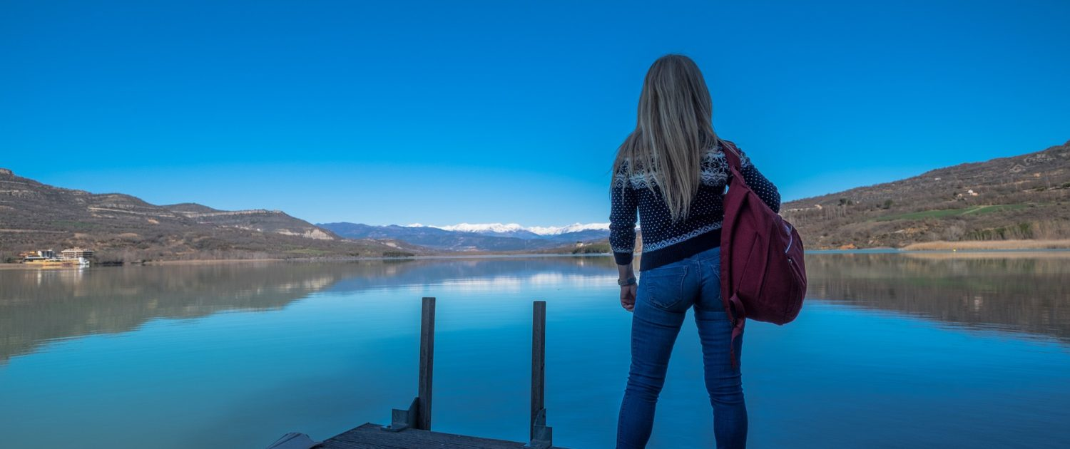 Traveller with red backpack standing on pier next to a lake