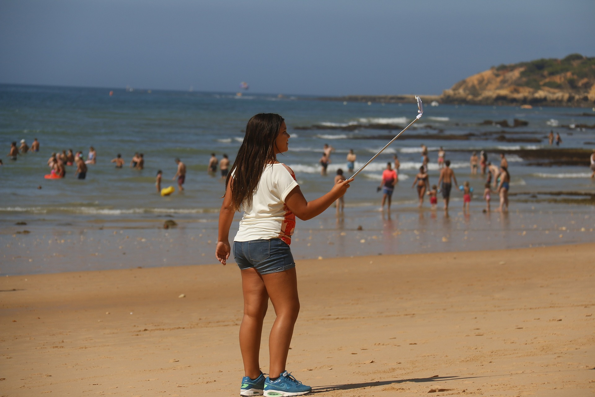 Woman on the beach taking photo with selfie stick