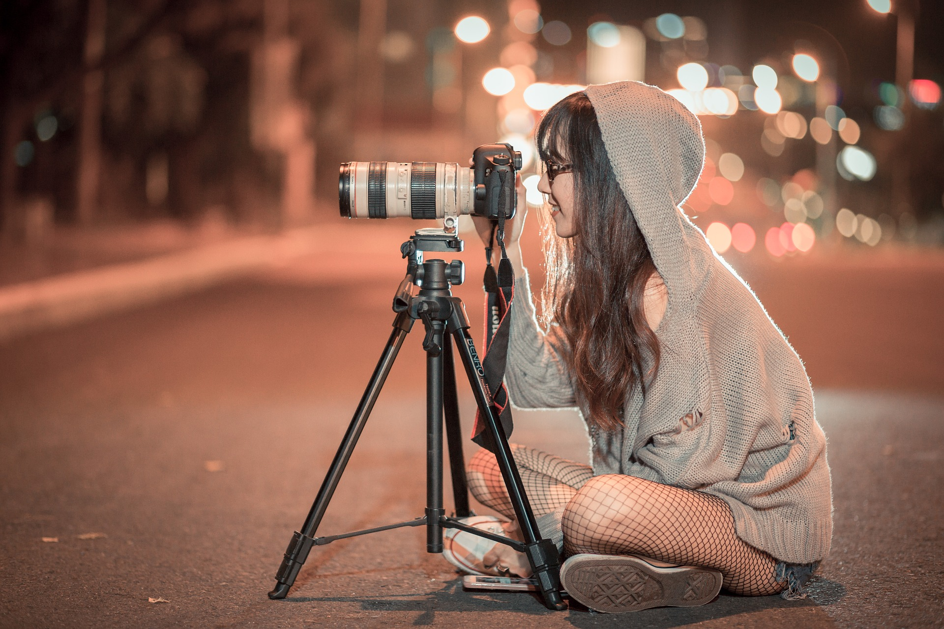 Woman sitting in street with camera taking pictures