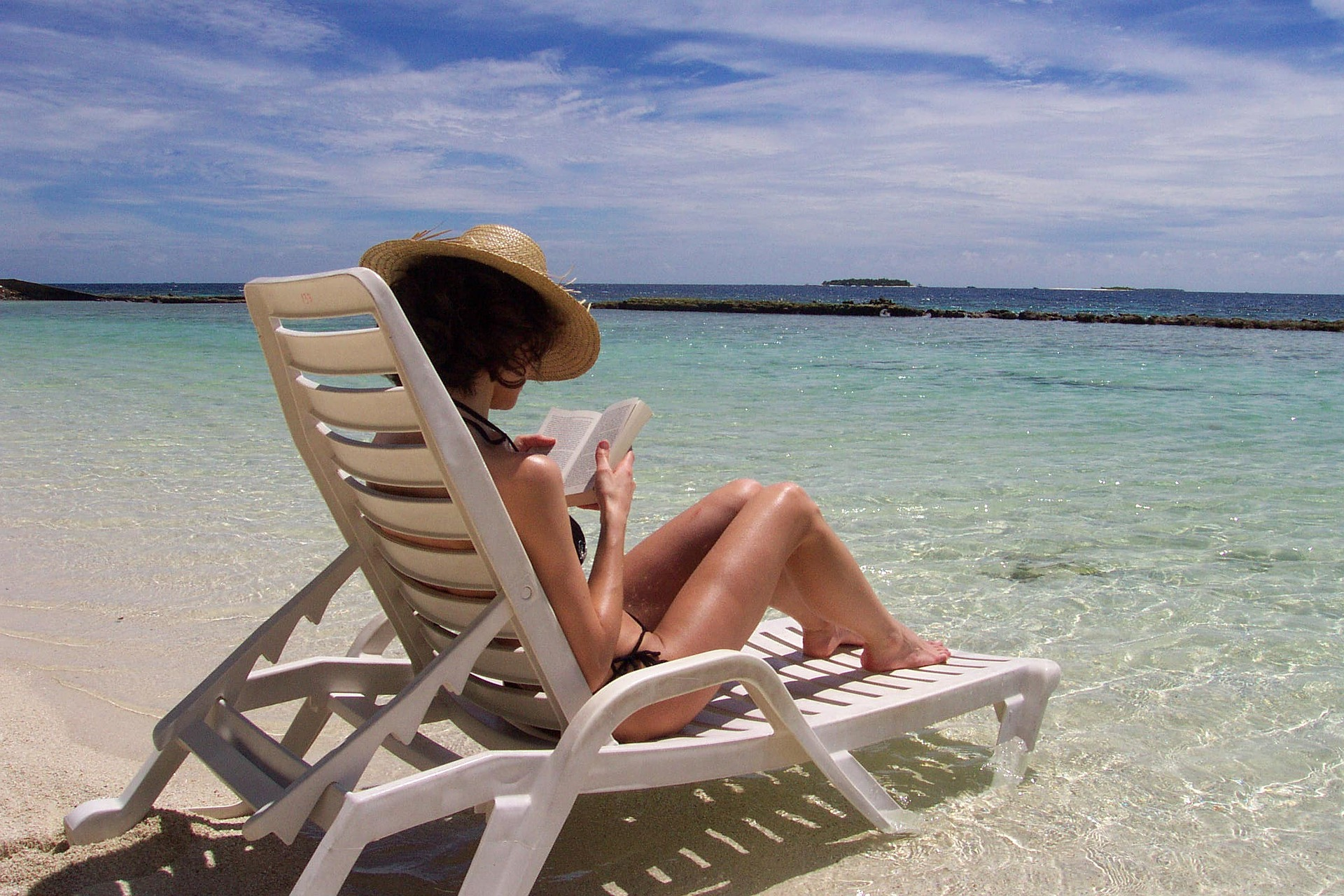 Woman sitting on beach in the Maldives