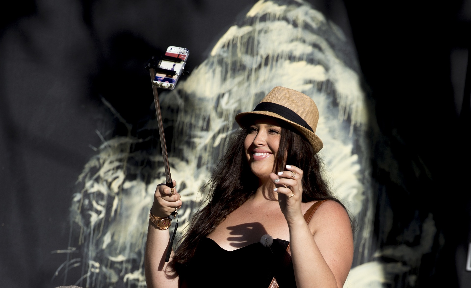 Woman smiling and taking photo with selfie stick