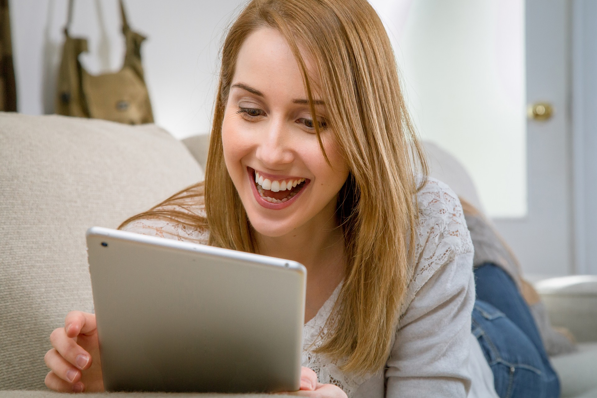 Woman smiling at tablet screen
