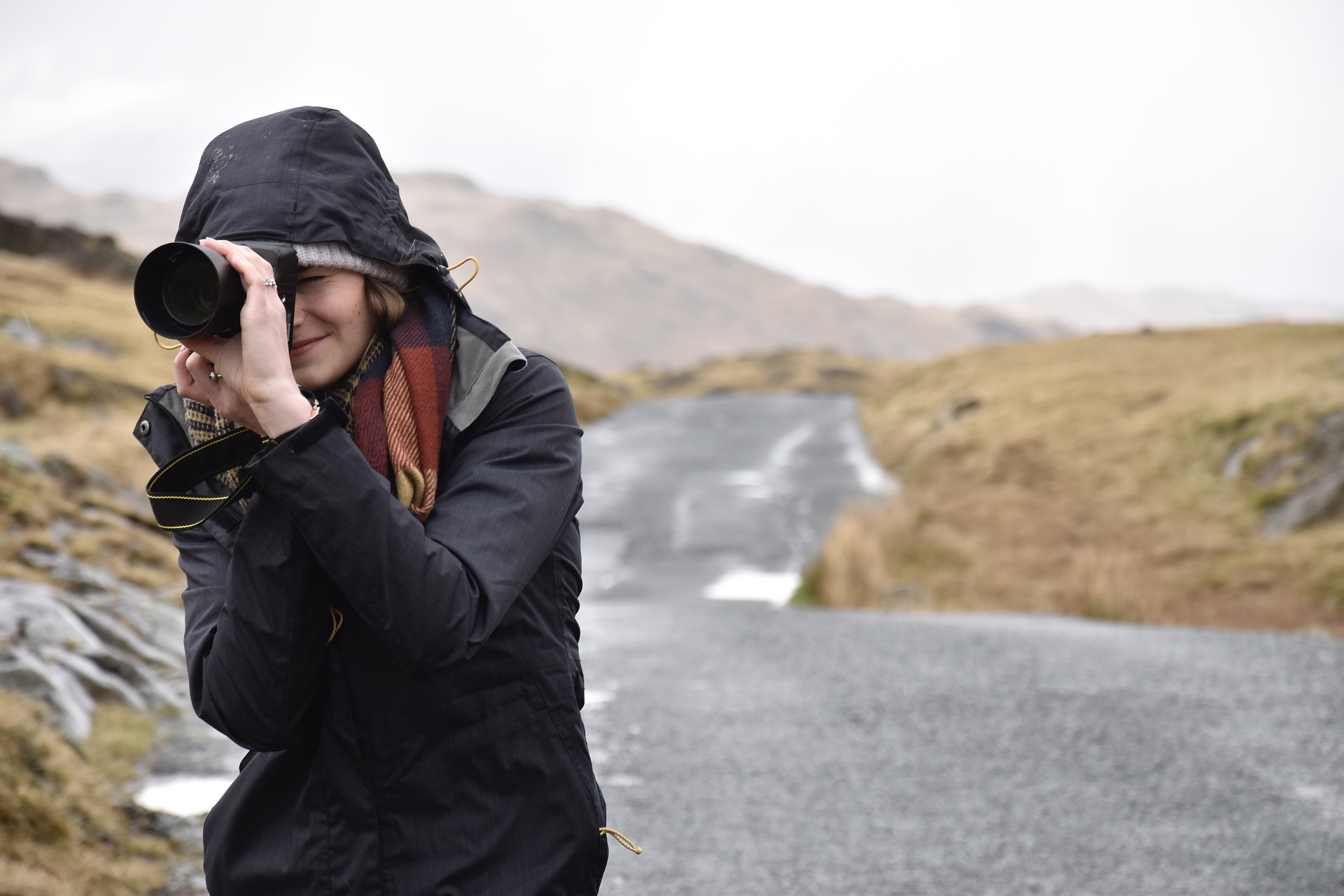 Woman with camera taking pictures in the road