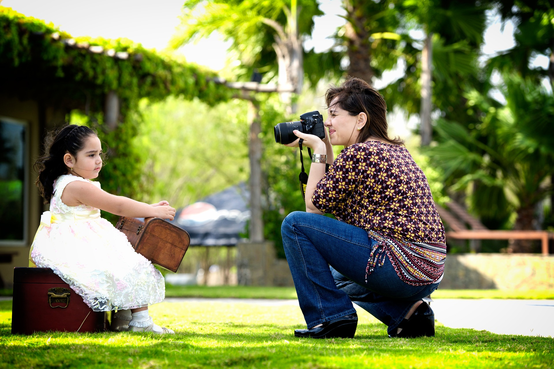 Woman with camera taking pictures of little girl
