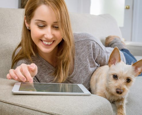 Woman with dog using tablet