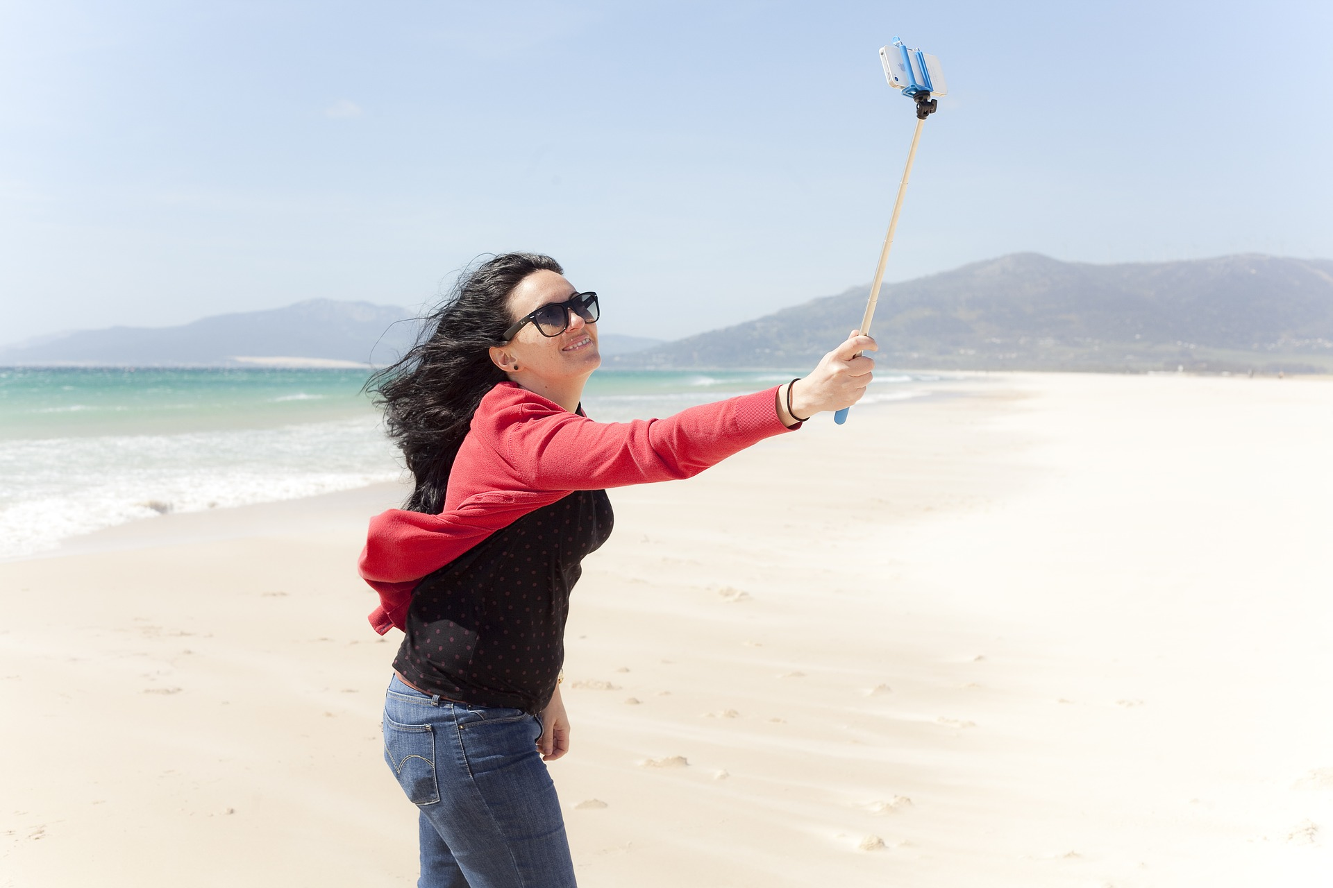 Woman with selfie stick on beach